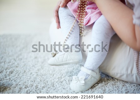 Legs of a toddler sitting on her mother�¢??s laps - stock photo