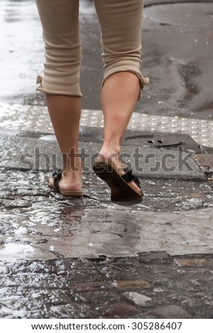 legs of a woman crossing a rainy street