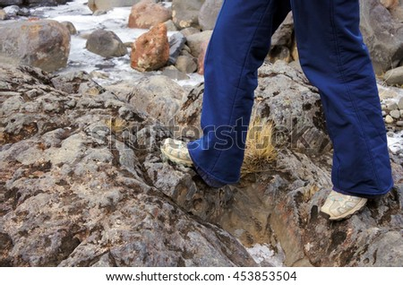 Legs of a woman hiker walks over rocks during hiking trip. Travel concept copy space - stock photo