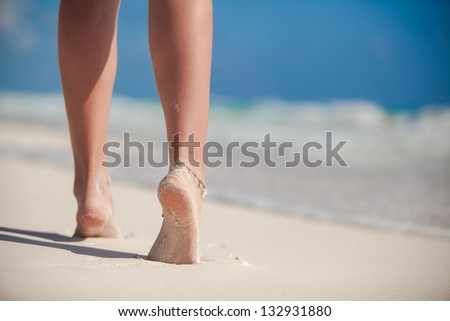 Legs of a woman walking at the tropical beach on the sand