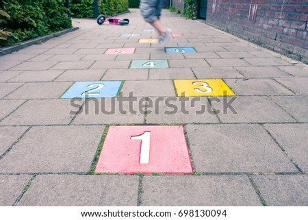 Legs of a young boy playing hopscotch in a playground