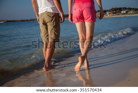 Legs of a young man and woman walking along the seacoast - stock photo