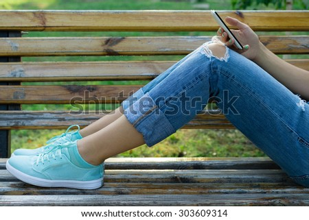 Legs of a young woman in jeans on a bench in the park. Girl resting in a park outdoors and uses a cell phone. Close-up. - stock photo