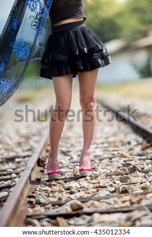 Legs of Asian model wearing black dress with the pink shoes , stand on the train track - stock photo