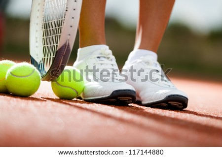 Legs of athlete near the tennis racket and balls - stock photo