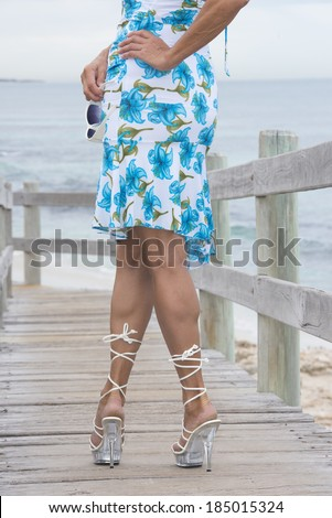 Legs of attractive mature woman posing confident with hand on hips and wearing high heel shoes outdoor, with ocean and sky as blurred background. - stock photo