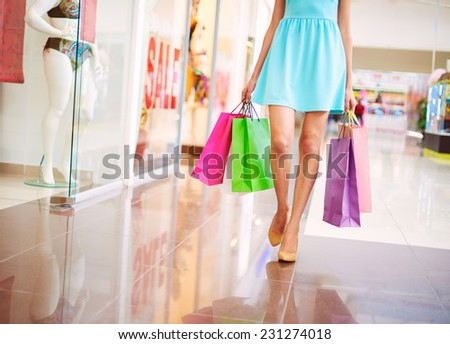 Legs of attractive shopaholic in blue dress walking down mall - stock photo