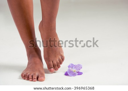 Legs of beautiful Afro American girl near an orchid flower, on a gray background, close up