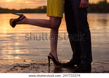 legs  of couple standing near the water at sunset