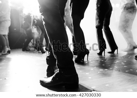 Legs of dancing people at the party - stock photo