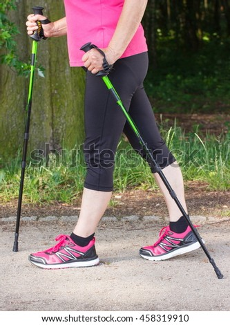 Legs of elderly senior woman in sporty shoes practicing nordic walking, healthy sporty lifestyles in old age