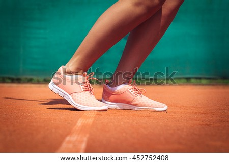 Legs of female tennis player. Close up image - stock photo