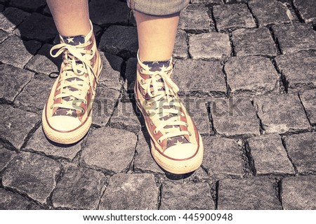 Legs of girl in gumshoes on pavement - stock photo