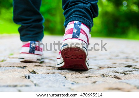 Legs of girl in gym shoes on pavement