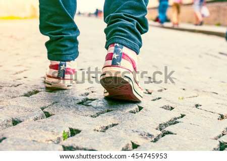 Legs of girl in sneakers on pavement. Toned image