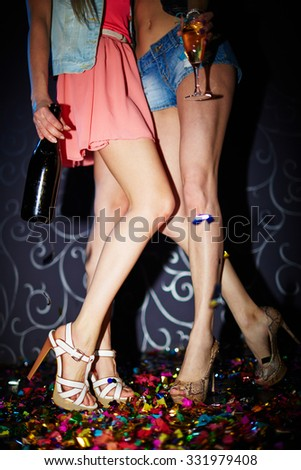 Legs of girls with champagne bottle and flute spending time in night club