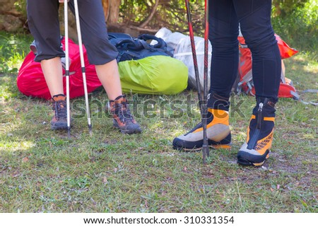 Legs of Hikers. Feet of Male and Female Backpackers in Heavy Alpine Boots Holding Walking Poles Staying on Green Meadow Lawn Packed Backpacks on Background - stock photo
