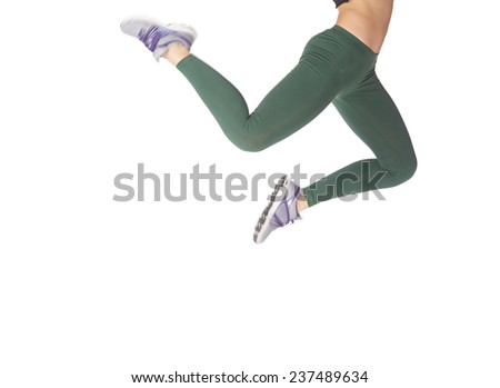 Legs of jumping sportive woman on a white background - stock photo