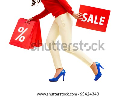 Legs of lady with red paper bags and sale card in move - stock photo