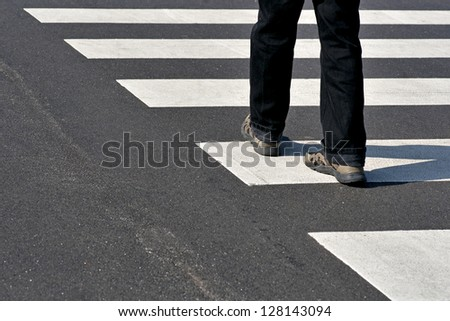 Legs of man in black jeans and sneakers crossing street - stock photo