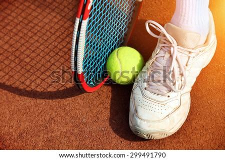 Legs of man near the tennis racquet and balls - stock photo