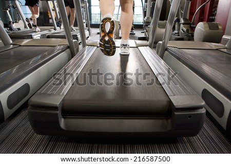 Legs of man running on treadmill in health club - stock photo