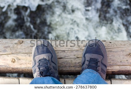 Legs of man standing on a wooden bridge over a torrent of water. - stock photo