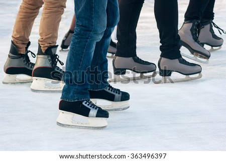 legs of people skating on winter day closeup