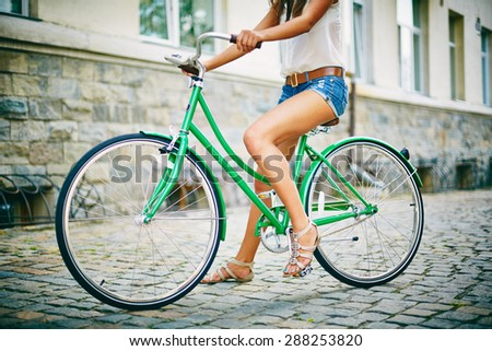 Legs of pretty girl sitting on bicycle in urban environment