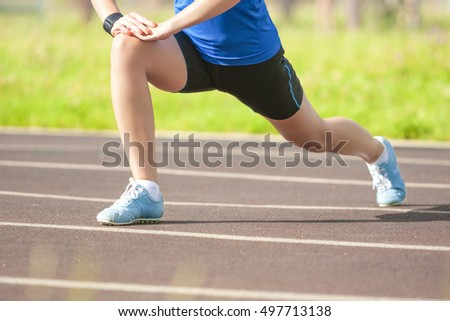 Legs of Professional Caucasian Female Athlete During Her Warming Up Exercises Outdoors. Horizontal Image