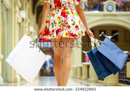 Legs of shopaholic wearing red dress while carrying several paperbags - stock photo