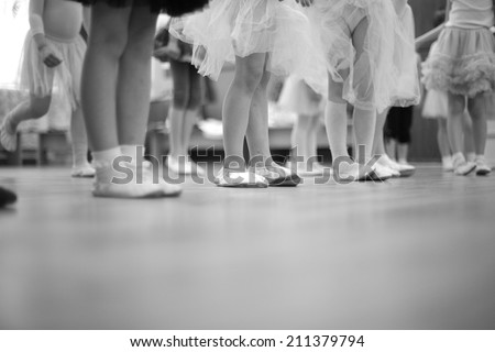 Legs of small girls in gymnastic slippers and fluffy skirts; monochrome - stock photo