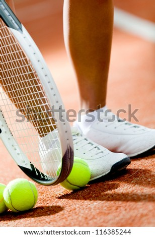 Legs of sportive girl near the tennis racket and balls - stock photo