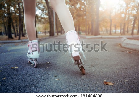 Legs of teenager having roller skate exercise in public park - stock photo