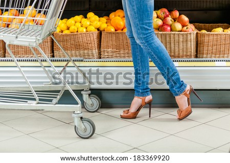 Legs of the female customer with cart against the shelves of fruits in the shop - stock photo