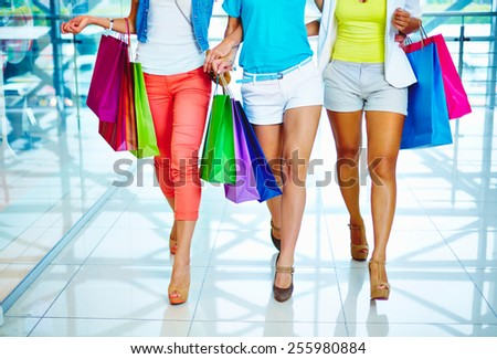 Legs of three consumers with paperbags walking down trade center - stock photo