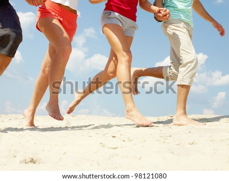 Legs of three friends running on beach in summer - stock photo