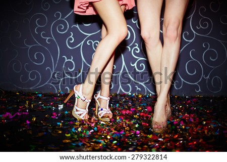 Legs of two girls dancing in night club - stock photo