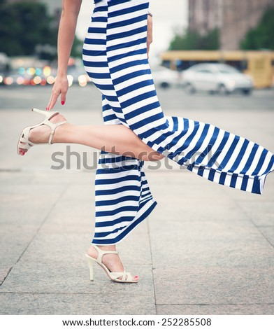 Legs of woman with high heels dressed long striped dress outdoor in the city - stock photo