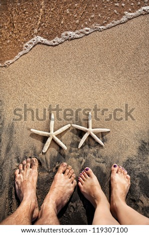 Legs of young couple standing on the beach near two starfishes on the sand with ocean near by - stock photo