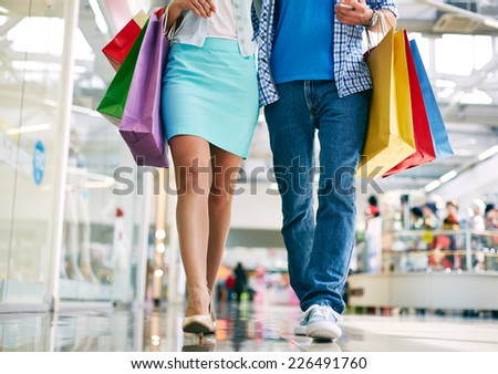 Legs of young couple with paperbags going in the mall - stock photo