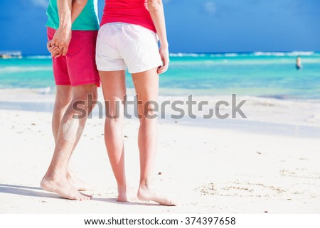 legs of young happy couple on tropical turquoise barbados beach