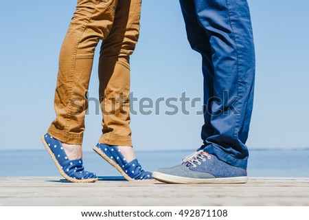legs of young hugging couple on the turquoise beach. Summer time