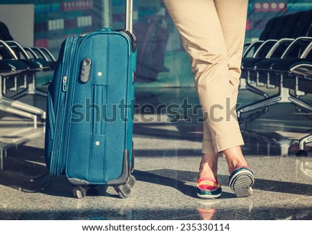 Legs of young woman close-up and blue baggage in airport - stock photo