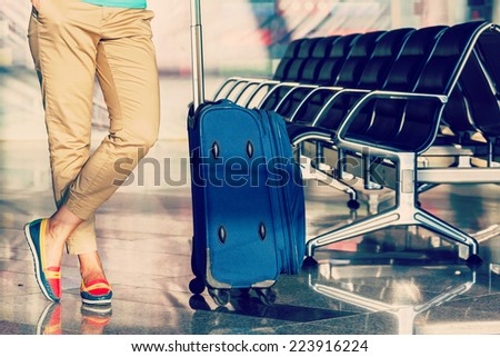 Legs of young woman close-up with baggage and chairs in airport - stock photo
