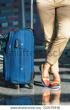 Legs of young woman close-up with baggage in airport - stock photo