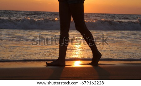 Legs of young woman going along ocean beach during sunrise. Female feet walking barefoot on sea shore at sunset. Girl stepping in shallow water at shoreline. Summer vacation concept. Close up.