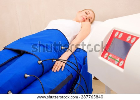 legs pressotherapy machine on woman in beauty center - stock photo
