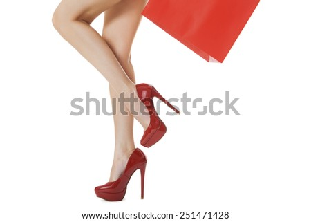 Legs Shot - Woman Legs with Flawless Skin in Red High Heels Shoes Lifting One Leg While Carrying Red Paper Bag. Isolated on White Background. - stock photo