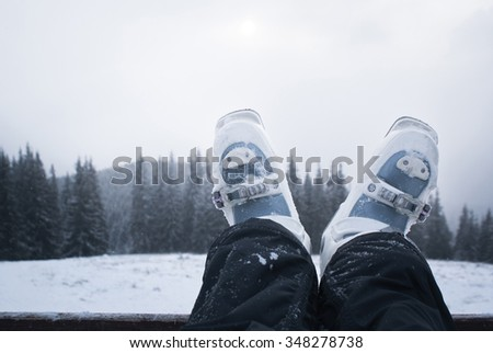 Legs skier in ski boots while relaxing after a day skiing. Mountain scenery away - stock photo